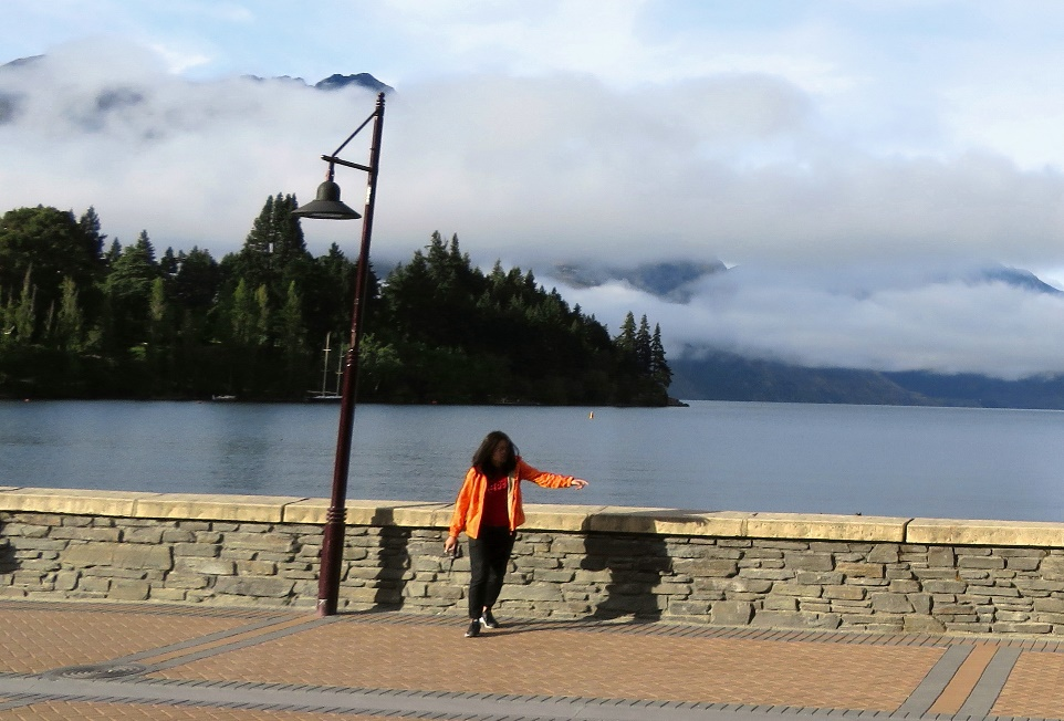 A person standing in front of a body of water Description automatically generated