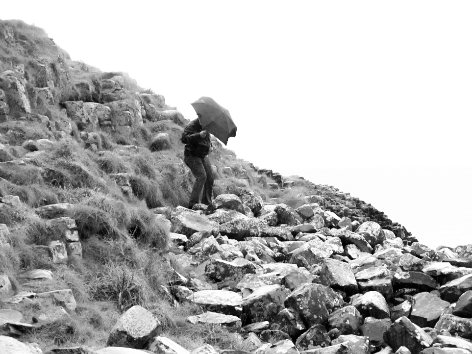 A person standing on a rocky hill Description automatically generated