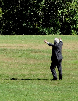 A person throwing a frisbee in a grassy field Description automatically generated